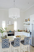 Bar stools with blue-and-white loose covers at breakfast bar in elegant, open-plan kitchen