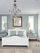 White wooden bed, chandelier and dove-grey walls in elegant bedroom