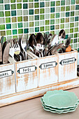 Cutlery stored in small labelled wooden boxes