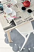 Dining table decoratively covered with newsprint decoupage