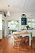 Dining table in country-house kitchen with doorway leading onto terrace with pergola