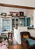Stools at island counter, in front of plate rack and antique wooden cupboard