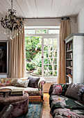 Crystal chandelier above sofas with vintage-style floral print and velvet ottoman