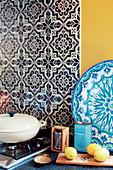 Schwarz-weiße Musterfliesen neben gelb gestrichener Wand über Küchenarbeitsfläche