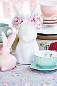 Osterhase mit Blumenschmuck auf nostalgisch gedecktem Tisch