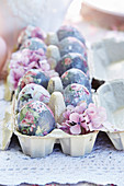 Decoupage floral eggs and purple flowers in egg box