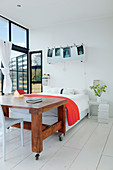Bed, wooden table on castors and steel-framed glass wall in light-flooded interior