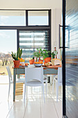 Dining table in light-flooded interior of eco-friendly pre-fab house
