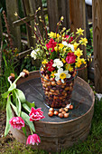 Colourful spring flowers and flower bulbs in glass vase