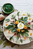 Cheese board decorated with leaves and flowers