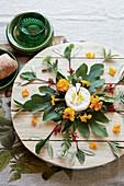 Käseplatte mit Blätter- und Blütendekoration