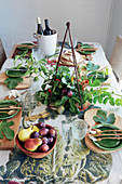 Fig leaves and flower arrangement decorating dining table set for autumn dinner