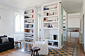 Floor-to-ceiling shelves used as partition element in open-plan interior