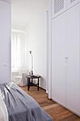 Blick vom Schlafzimmer mit deckenhohem Kleiderschrank auf Sitzecke am Fenster