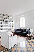 Sitzbereich mit Sofa und Hussensesseln neben Raumteilerwand