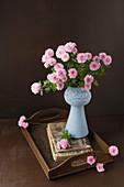 Rosa Asternstrauß in Vase auf antikem Holztablett