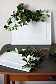 Ivy tendrils on framed pictures painted over in white on old table