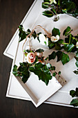 Ivy tendrils and fabric flowers arranged with framed pictures painted over in white
