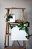 Ivy tendrils, fabric flowers and framed pictures painted over in white arranged on ladder