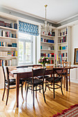 Dining area surrounded with white fitted shelving