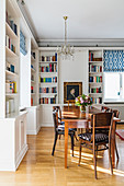 Dining area surrounded by white fitted shelving