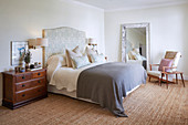 Chest of drawers used as bedside table next to bed with upholstered headboard
