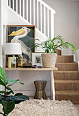 Pictures, lamp and houseplant on table next to foot of stairs