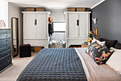 Bed and wardrobes in sleeping area on gallery of penthouse apartment