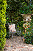 Metal chair next to planted urn in romantic seating area in garden