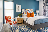 Blue and white bedroom with orange accents