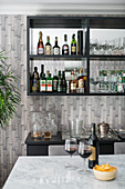 Home bar; bottles of spirits and glasses on mirrored shelves