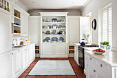 White, country-house-style kitchen with collection of blue-and-white crockery on dresser