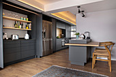 Charcoal-grey kitchen cabinets running through two rooms with chairs at small island counter