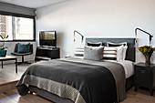 Graues Doppelbett neben Sitzbereich auf Podest in Einzimmer-Apartment