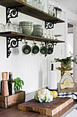 Vintage-style crockery on wooden shelves on wrought iron brackets
