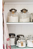 Vintage-style storage jars on kitchen shelves