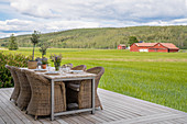 Table and wicker chairs on deck with view of fields and woods