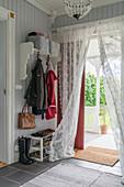 Fluttering curtains on open front door in rustic foyer