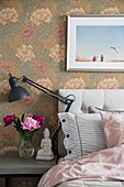 Vase of peonies next to bed against floral art nouveau wallpaper