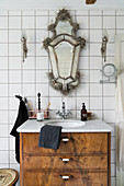 Antique Venetian mirror and sconce lamps above washstand
