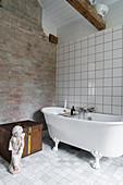 Classic free-standing bathtub next to rustic brick wall