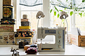Sewing machines and stack of old tins in front of window