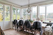 Grey sheepskin rugs on chairs around dining table in conservatory