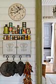 Alte Blechdosen und Gewürze auf einem Wandschränkchen