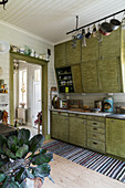 Old fitted kitchen with green, retro-style cabinets