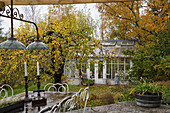View of conservatory in autumnal garden seen from terrace