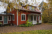 Falu-red Swedish house with porch in autumnal garden