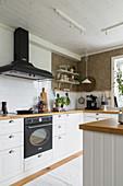 Küche in klassischem Landhausstil mit weißer Front, weiße Spritzschutfliesen und Tapete