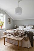 Double bed and bedroom bench in bedroom with pale grey walls