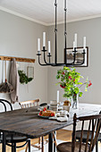 Old table with wooden top and chairs below cast iron candle chandelier in dining area